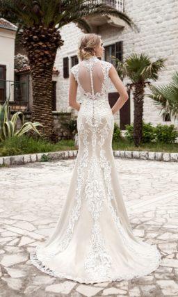 Кружевное свадебное платье облегающего кроя с полупрозрачной спинкой и фигурным высоким воротником.