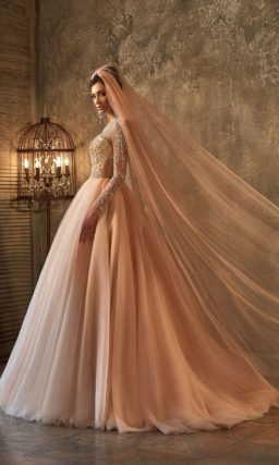 Закрытое свадебное платье кремового оттенка с длинными рукавами и кружевной вставкой сзади.