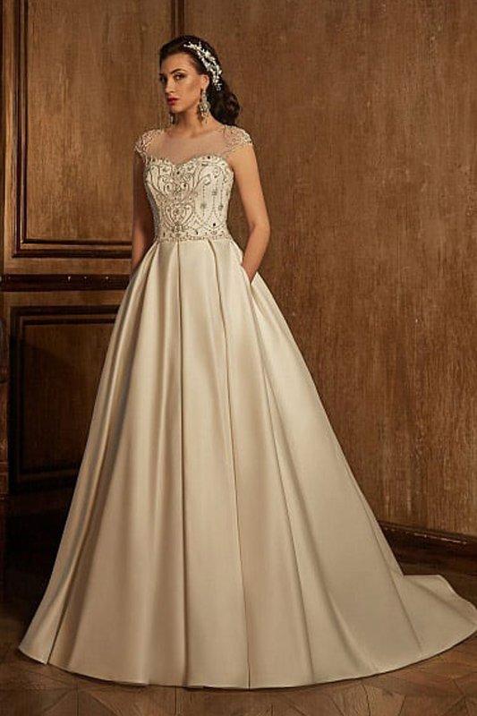Атласное свадебное платье с верхом, закрытым полупрозрачной тканью, и скрытыми карманами.