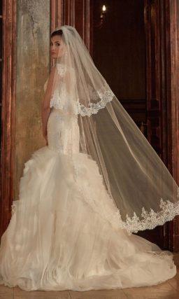 Великолепное свадебное платье «русалка» с покрытой оборками юбкой и облегающим вышитым верхом.