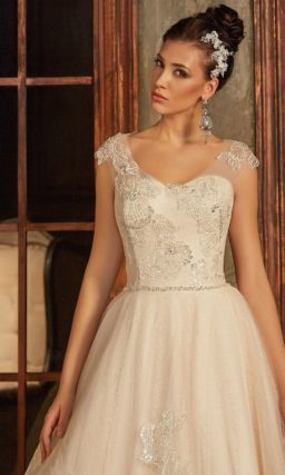 Свадебное платье оттенка слоновой кости, украшенное кружевом по объемной юбке со шлейфом.
