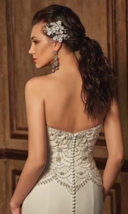 Свадебное платье с потрясающим шлейфом, дополняющим прямую юбку, и расшитым корсетом.