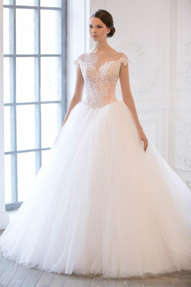 Кружевное свадебное платье с прозрачной отделкой декольте и многослойной юбкой.