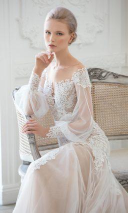 Элегантное свадебное платье с бежевой подкладкой и широкими прозрачными рукавами.