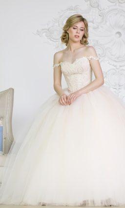 Пышное свадебное платье с фигурными бретельками на предплечьях и кружевным корсетом.