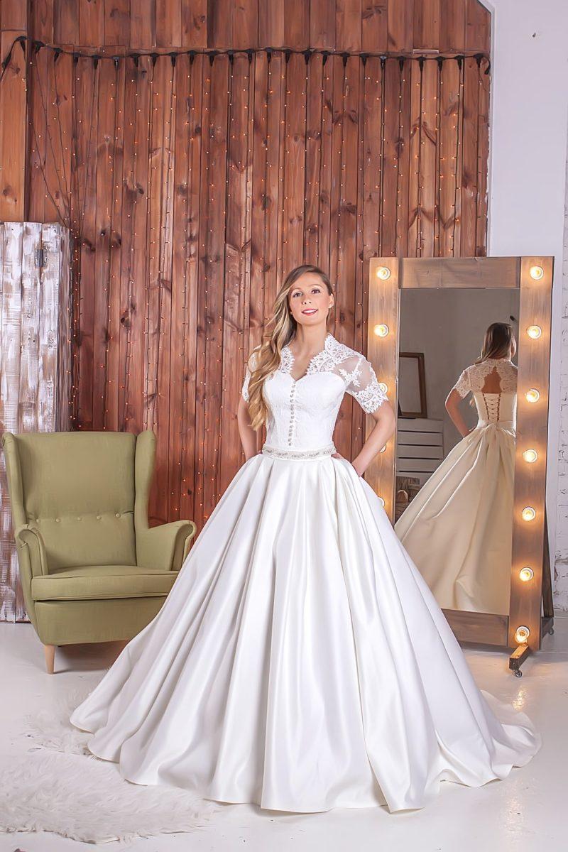 Элегантное свадебное платье с V-образным декольте и кружевными рукавами до локтя.