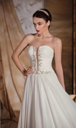 Выразительное свадебное платье с глубоким декольте, оформленным по краям вышивкой.