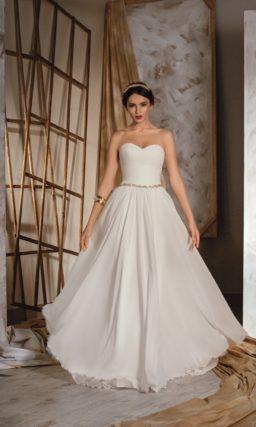 Женственное свадебное платье с лифом в форме сердца и узким серебристым поясом на талии.
