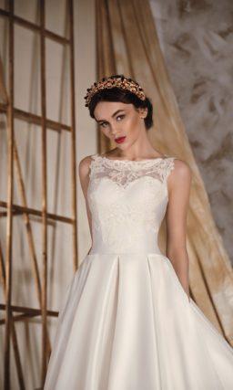 Атласное свадебное платье с пышной юбкой со скрытыми карманами и кружевным закрытым верхом.