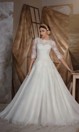 Закрытое свадебное платье со сногсшибательно пышной юбкой и кружевным верхом с рукавом.