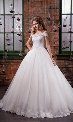 Пышное свадебное платье с кружевным портретным вырезом и многослойной юбкой со шлейфом.