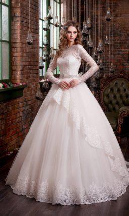 Закрытое свадебное платье с пышной баской и кружевной отделкой верха с длинным рукавом.