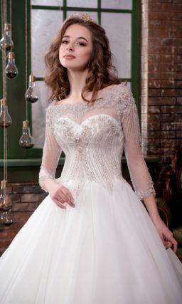 Роскошное свадебное платье с изысканной юбкой и длинными рукавами, украшенными вышивкой.