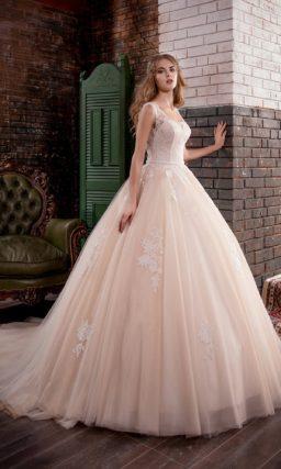 Пышное бежевое свадебное платье с округлым декольте и открытой спинкой.