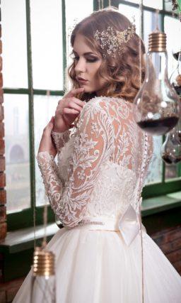 Великолепное свадебное платье с сияющим поясом и длинными кружевными рукавами.
