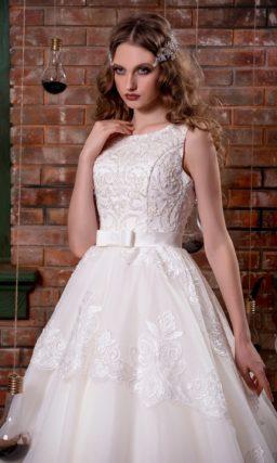 Кружевное свадебное платье с пышной многослойной юбкой и изящным поясом на талии.