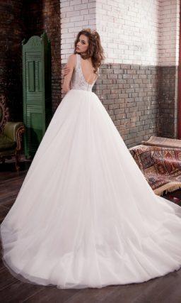 Романтичное свадебное платье пышного кроя с глубоким округлым декольте на спине.