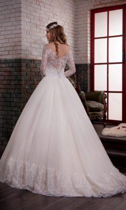 Потрясающе пышное свадебное платье с кружевным декором и узким блестящим поясом.
