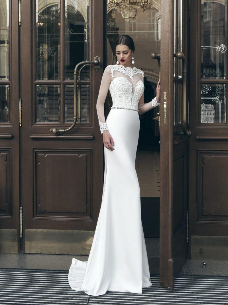 Закрытое свадебное платье с длинными рукавами и атласной юбкой прямого кроя.