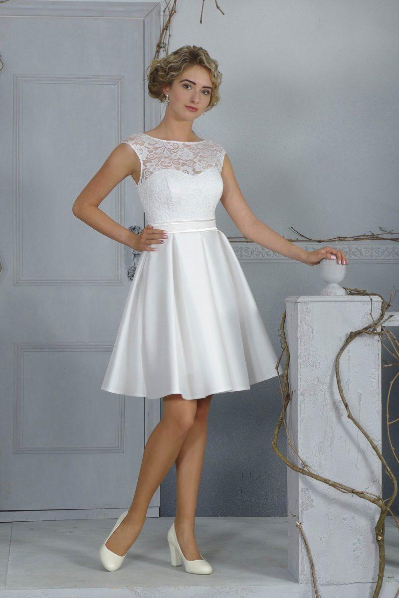 Атласное свадебное платье с юбкой длиной до колена и верхом, покрытым кружевной тканью.