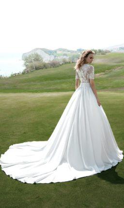 Атласное свадебное платье с элегантным поясом на талии и короткими кружевными рукавами.