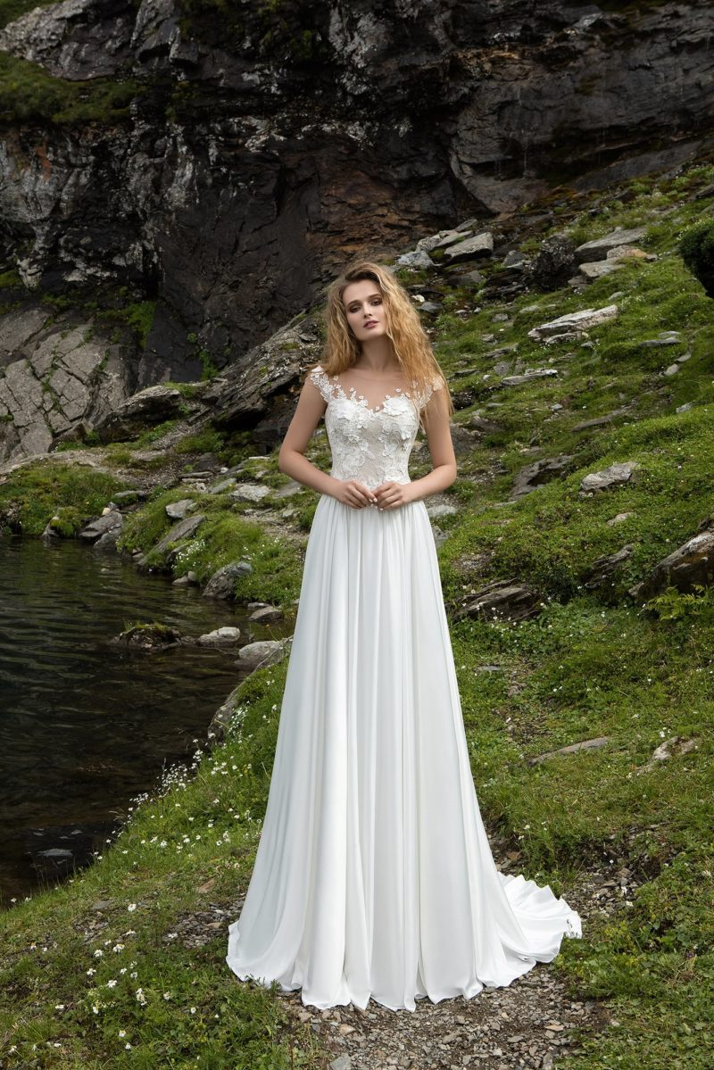 Прямое свадебное платье с нежными вертикальными складками по подолу и кружевным лифом.