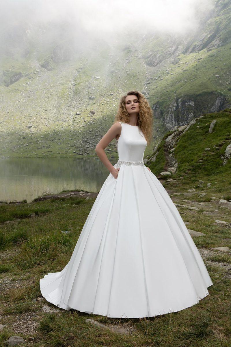 Утонченное свадебное платье пышного кроя с закрытым лифом и сияющим поясом на талии.