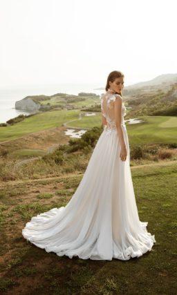 Эксцентричное свадебное платье с разрезом на юбке прямого кроя и объемным декором верха.