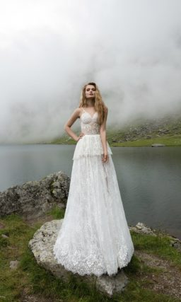 Кружевное свадебное платье с узкими бретелями, пышной баской и юбкой прямого кроя.