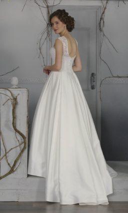 Пышное свадебное платье с роскошной атласной юбкой со шлейфом и закрытым кружевным лифом.