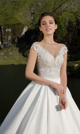 Атласное свадебное платье с объемной юбкой и кружевным верхом с V-образным декольте.