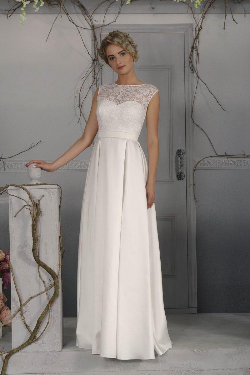 Прямое свадебное платье с широким поясом и округлым вырезом, обрамленным кружевом.