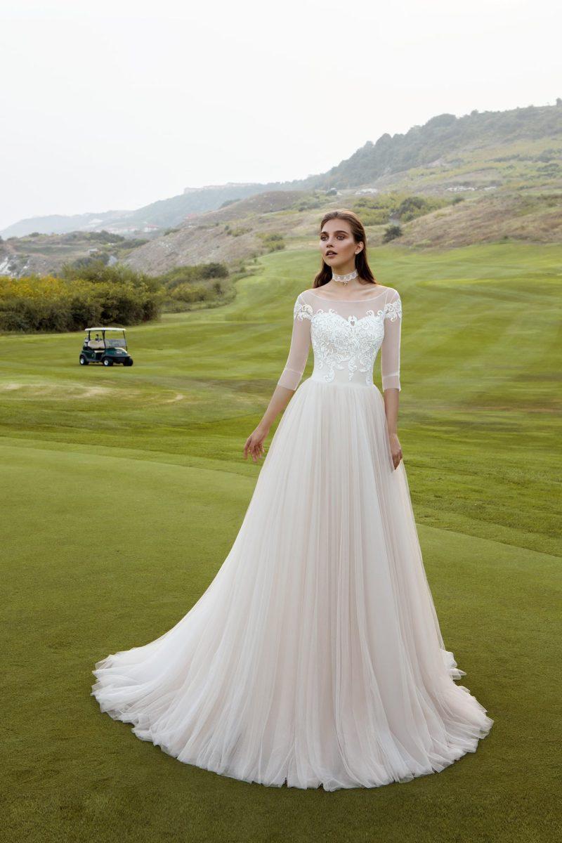 Пышное свадебное платье с изящным поясом, полупрозрачными рукавами и вырезом бато.