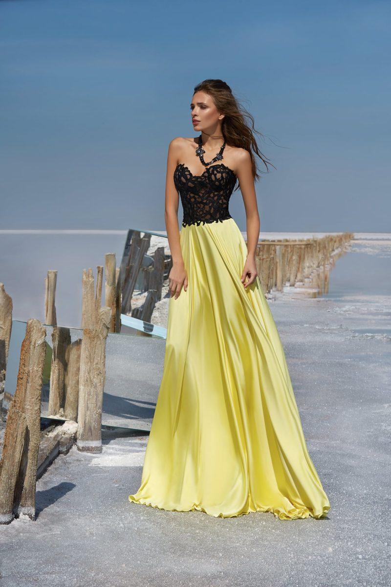 Вечернее платье с открытым черным корсетом и желтой атласной юбкой.