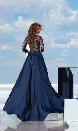 Синее вечернее платье с глубоким фигурным декольте и длинным рукавом.
