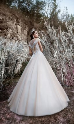 Роскошное пышное свадебное платье цвета слоновой кости с кружевным декором верха.