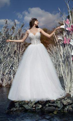 Пышное свадебное платье с романтичной юбкой и кружевной отделкой облегающего верха.