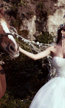 Открытое свадебное платье с роскошной многослойной юбкой и фактурным корсетом.