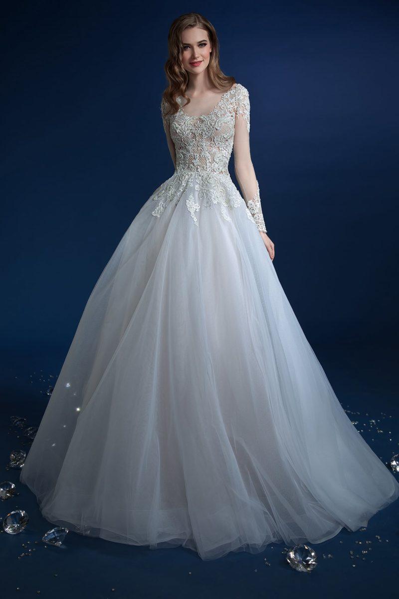 Воздушное свадебное платье с многослойным подолом и длинными рукавами.