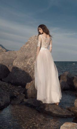 Бежевое свадебное платье с многослойной прямой юбкой и кружевным рукавом.