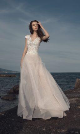 Кружевное свадебное платье кремового цвета с тонкой верхней юбкой.