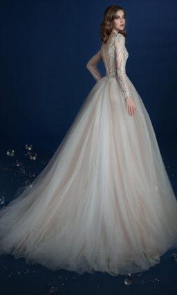 Свадебное платье с пышной верхней юбкой, покрытое кружевной отделкой.