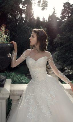 Пышное свадебное платье с длинным полупрозрачным рукавом.
