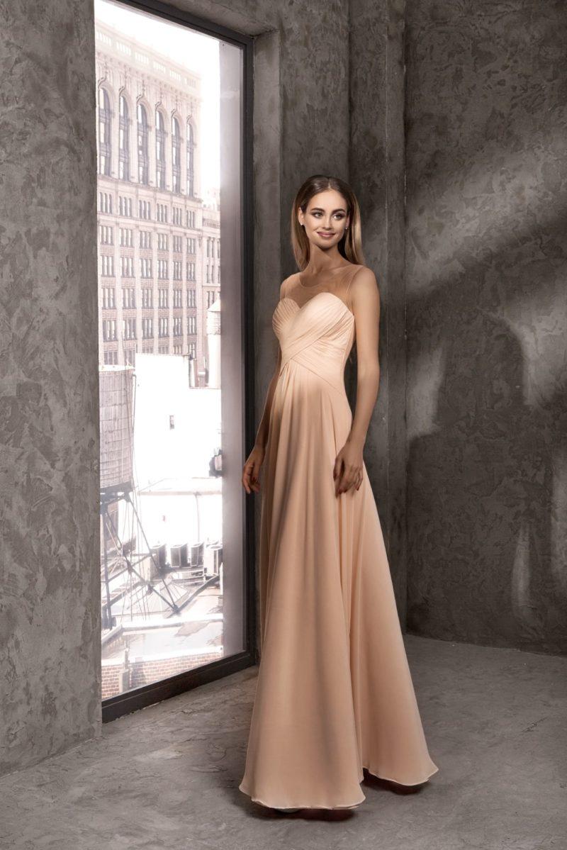 Кремовое вечернее платье с открытым лифом и драпировками.