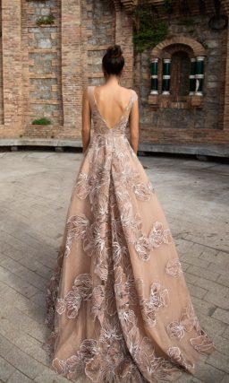 Пышное вечернее платье бежевого цвета, украшенное вышивкой.