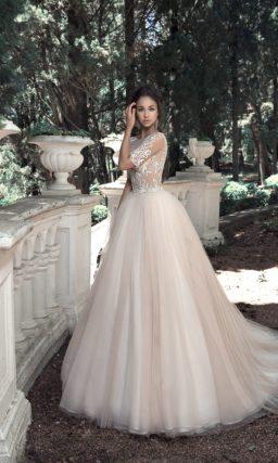 Романтичное свадебное платье с полупрозрачным верхом и бежевой юбкой.
