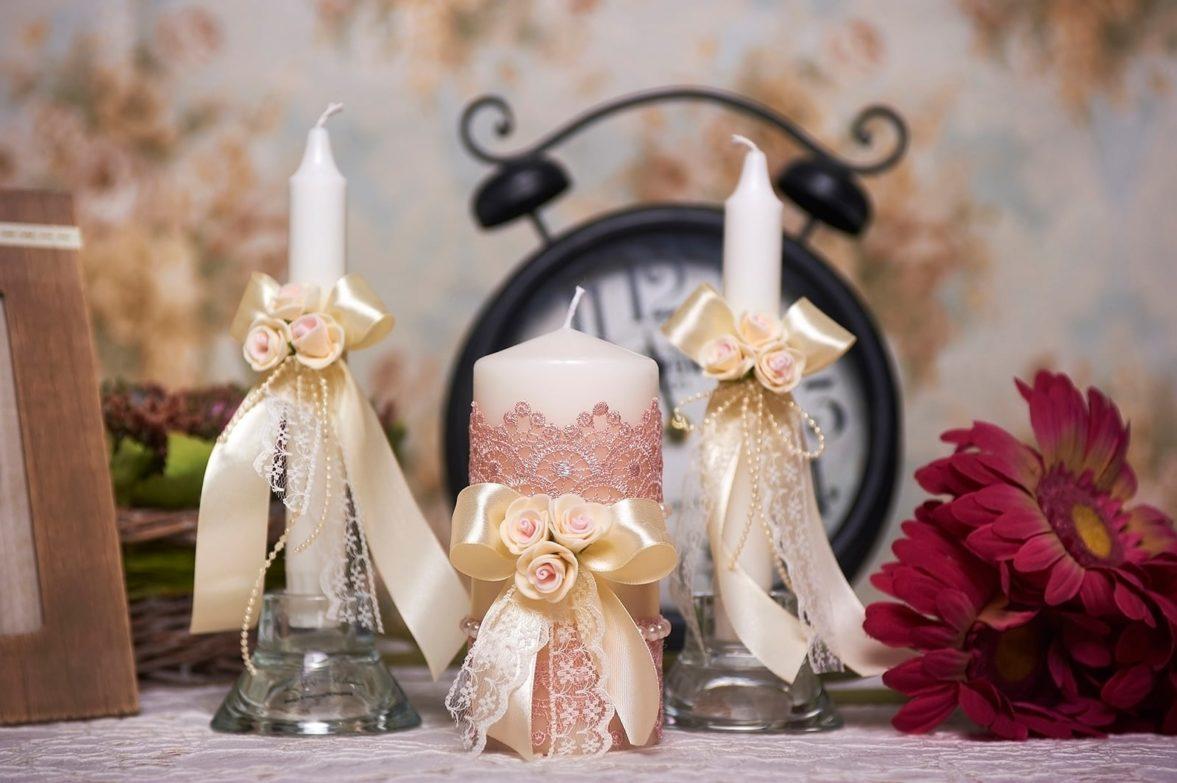 Свадебные свечи с кремовыми атласными бантами и бутонами.