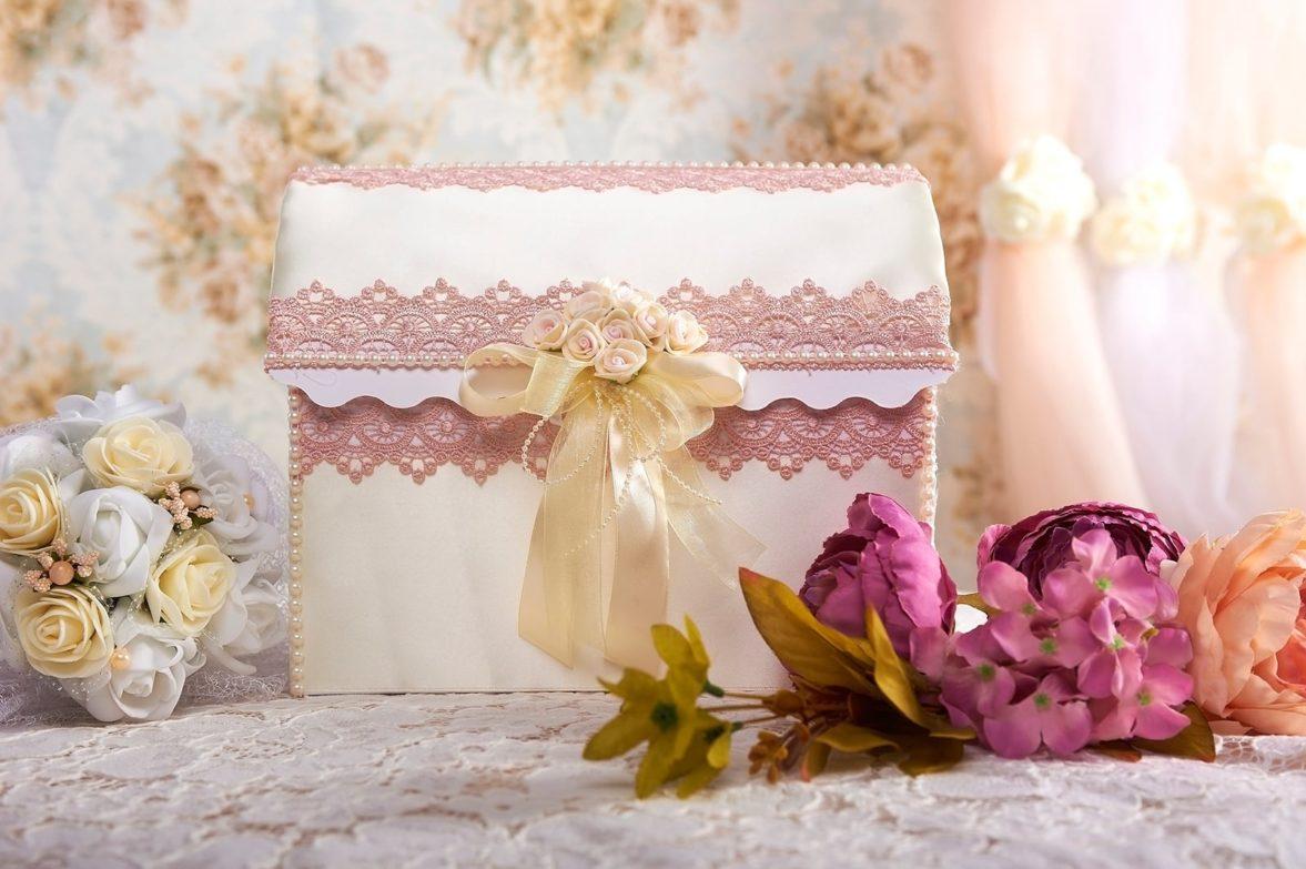 Свадебная корзинка цвета слоновой кости с кремовым бантом и розовым кружевом.