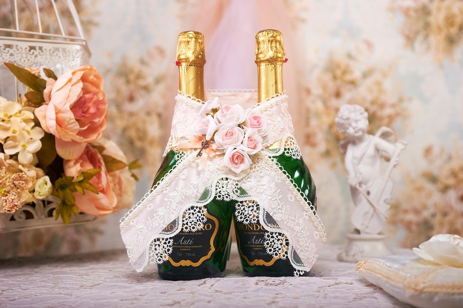 Розовое украшение на шампанское, декорированное бутонами.