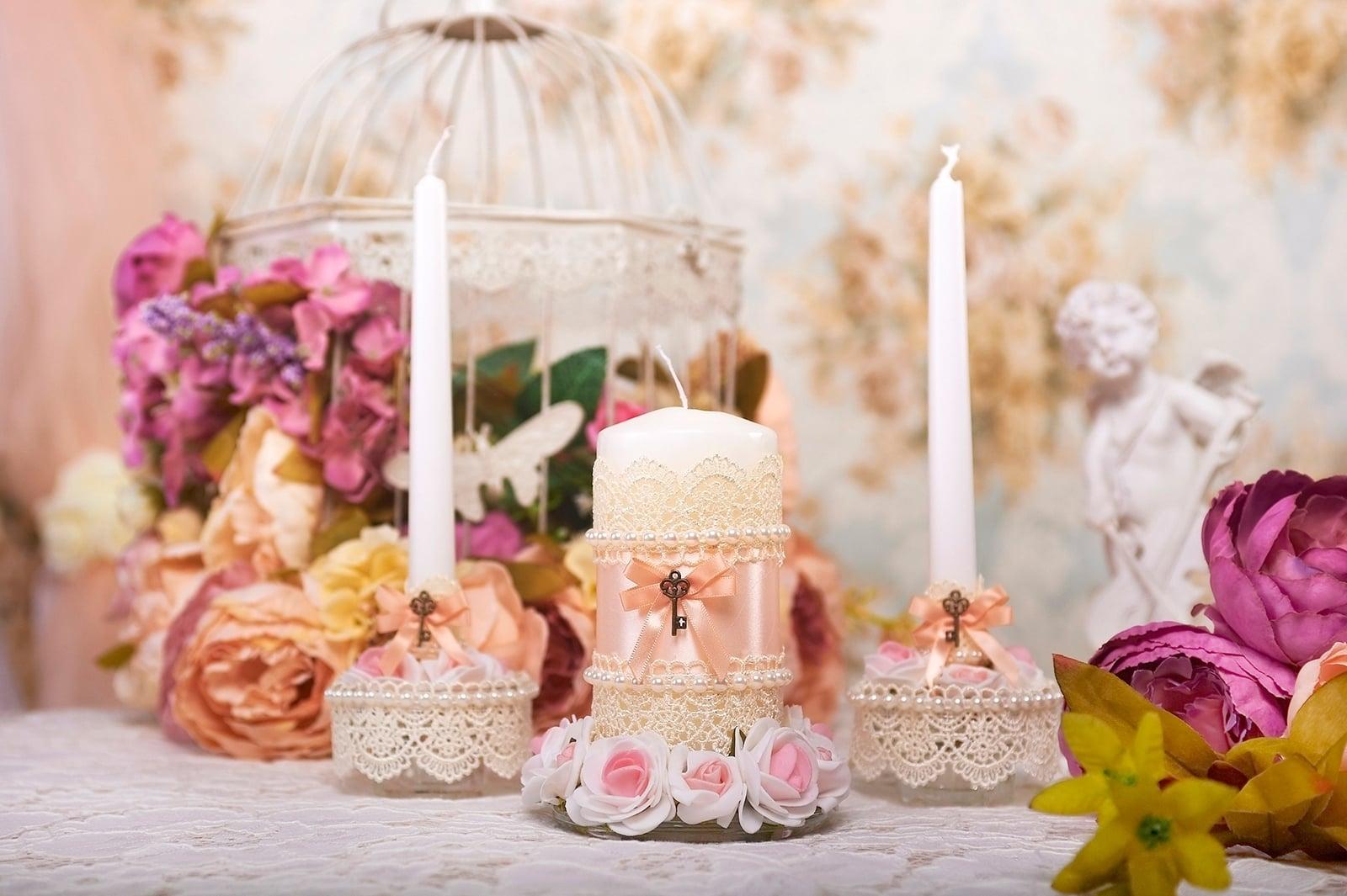 Свадебные свечи с розовыми бантами и декоративными ключиками.